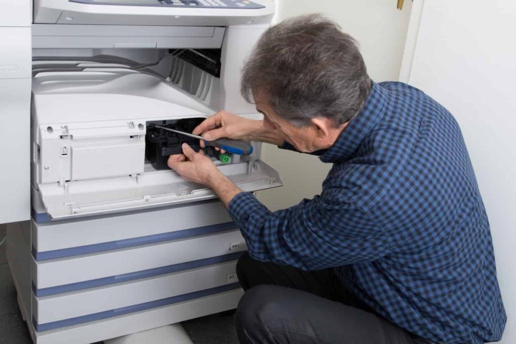 Man fixing a copier