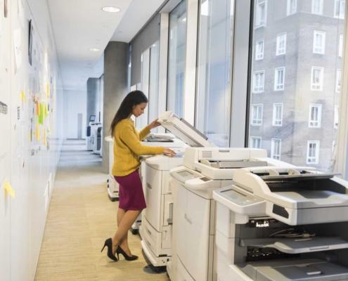 Full length of businesswoman using photocopier