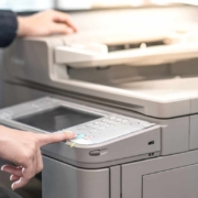 Male hand pushing button on photocopier copying and printing report paperwork in office. Electronic equipment and supply for business organization.