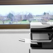 """big grey copier in grey office and color life beyond window (MFP (Multi Function Product/ Printer/ Peripheral), multifunctional, all-in-one (AIO), or Multifunction Device (MFD), is an office machine )"""