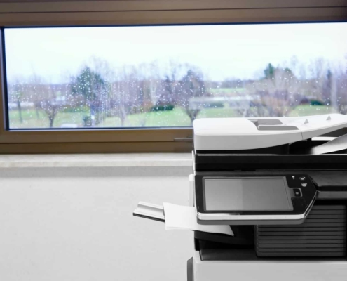 """""""big grey copier in grey office and color life beyond window (MFP (Multi Function Product/ Printer/ Peripheral), multifunctional, all-in-one (AIO), or Multifunction Device (MFD), is an office machine )"""""""