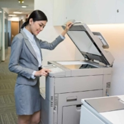 Smiling Vietnamese secretary scanning a document