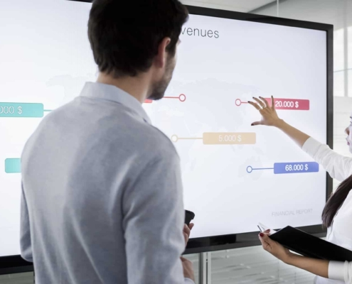 Male and female colleague discussing financial diagrams on large screen in meeting room and preparing for presentation